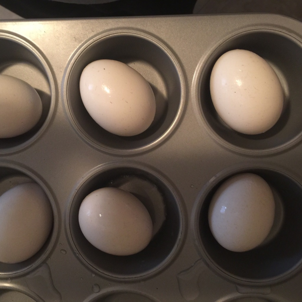 This recipe is the best...courtesy of Food Network. Place the eggs in the muffin pan and bake for 25 mins on 325 degrees.As soon as they are removed from the oven, put the eggs in a bowl of ice water. Let sit for 10-15 more minutes.